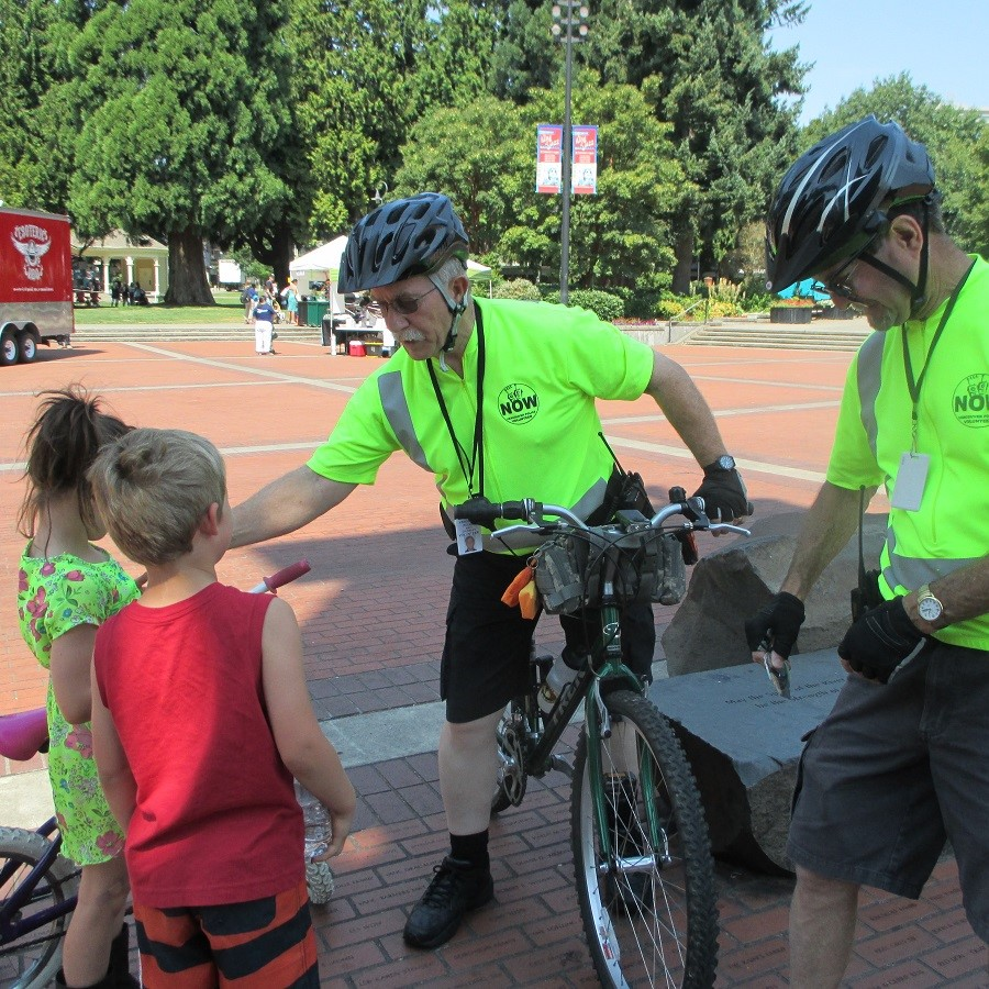 Two citizen patrol volunteers in bright yellow shirts are sanding with their bikes and talking to two children.