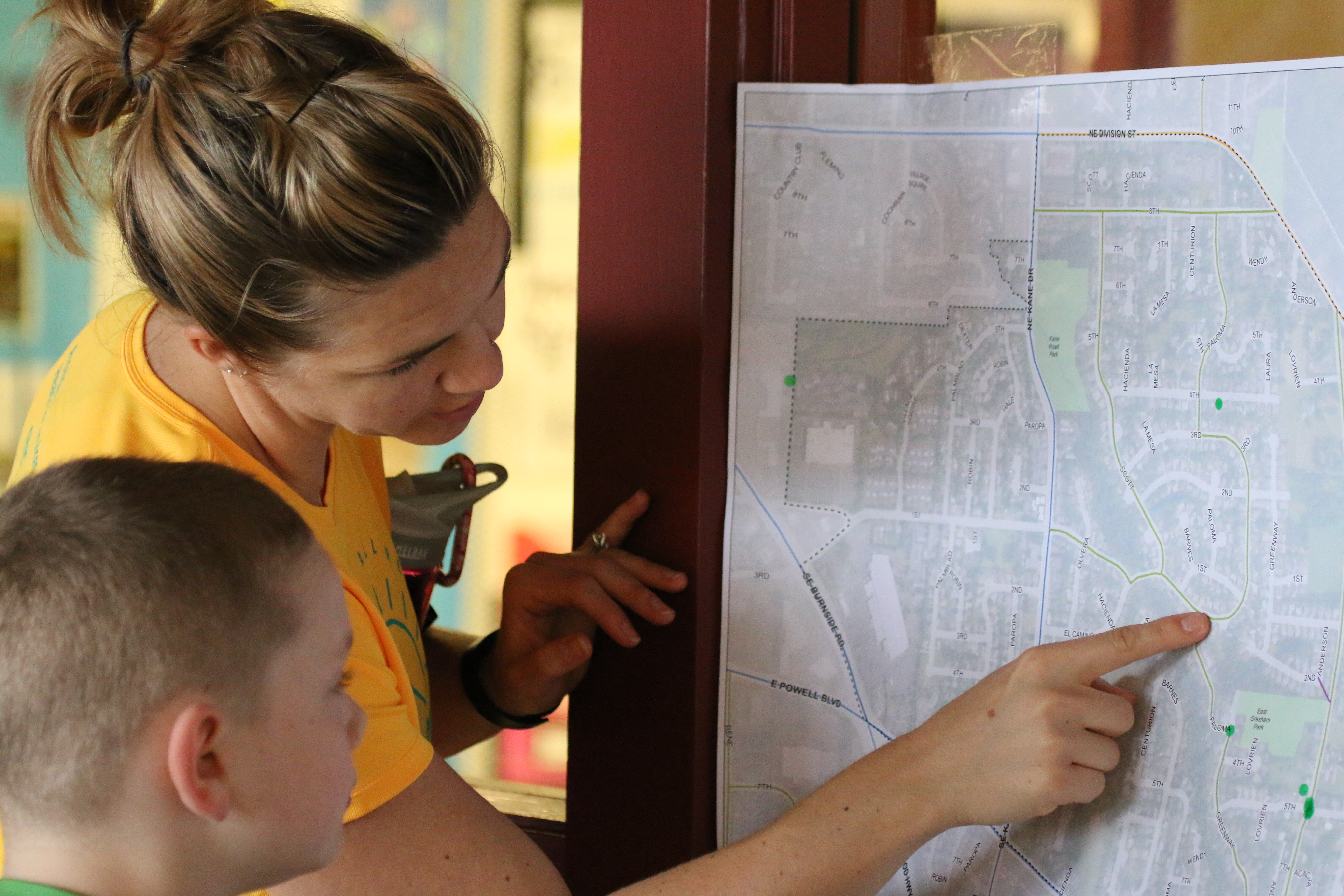 Woman points to a map and talks to a boy who is looking at the map.
