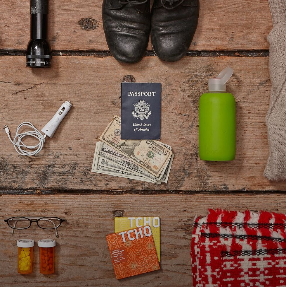 Emergency supplies are laid out on a wooden floor. Includes flashlight, shoes, sweater, cell charger, cash, passport, water bottle, glasses, prescription drugs, chocolate, and a blanket.