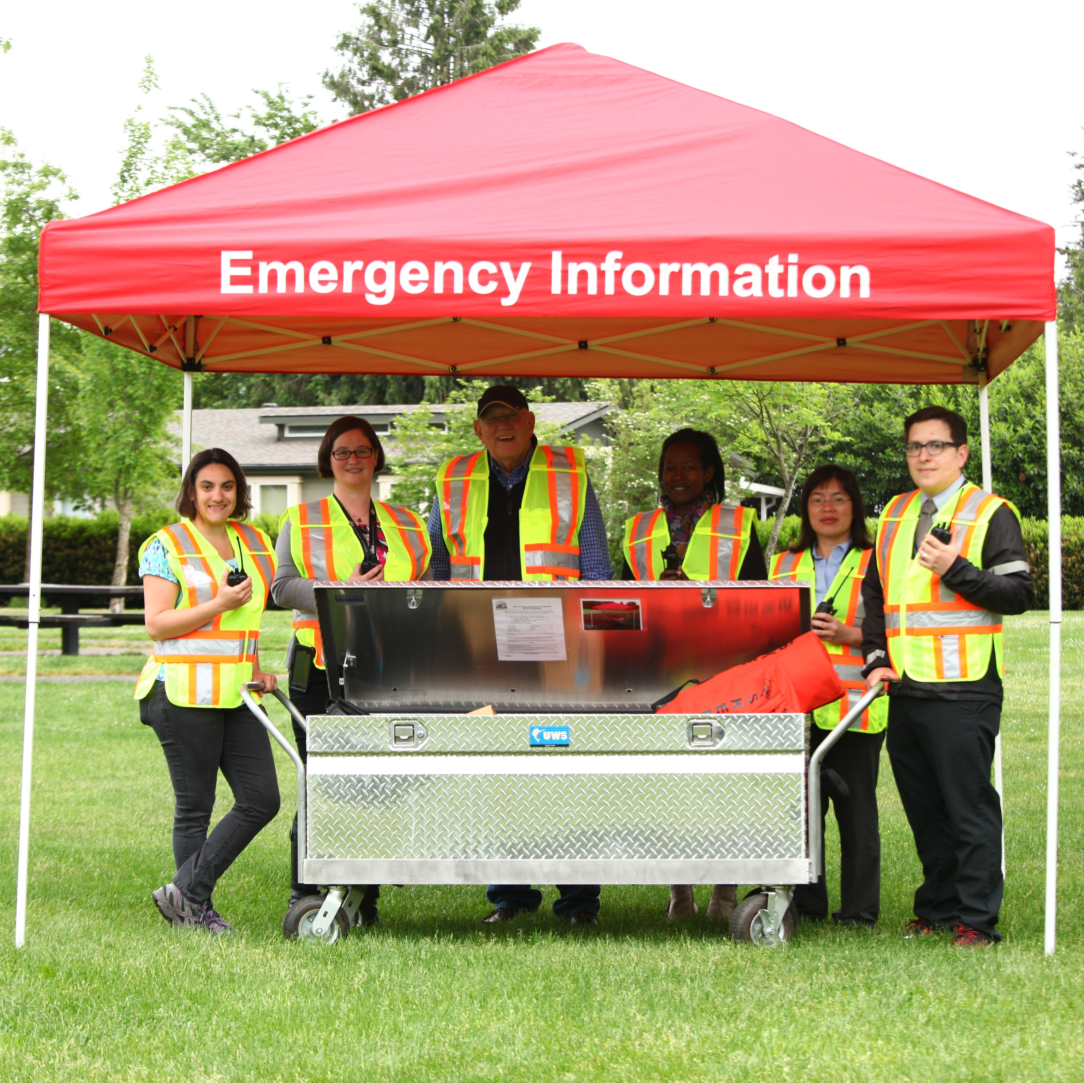 "Volunteers in yellow safety vests stand around a BEECN box under a red pop-up tent that says ""Emergency Information"" on it."