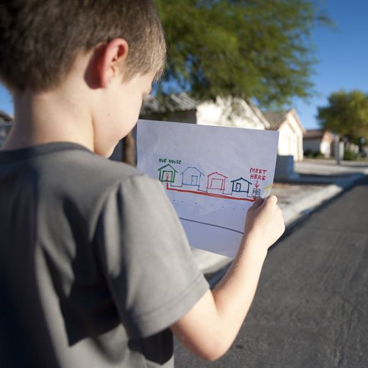 Young Caucasian boy stands on a suburban street. He is holding a hand-drawn map of his neighborhood with his house and a meeting spot labeled.