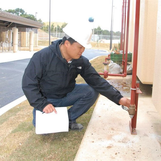Building inspector wearing hard hat and carrying paper and pen is kneeling on one knee and looking at a pipe.