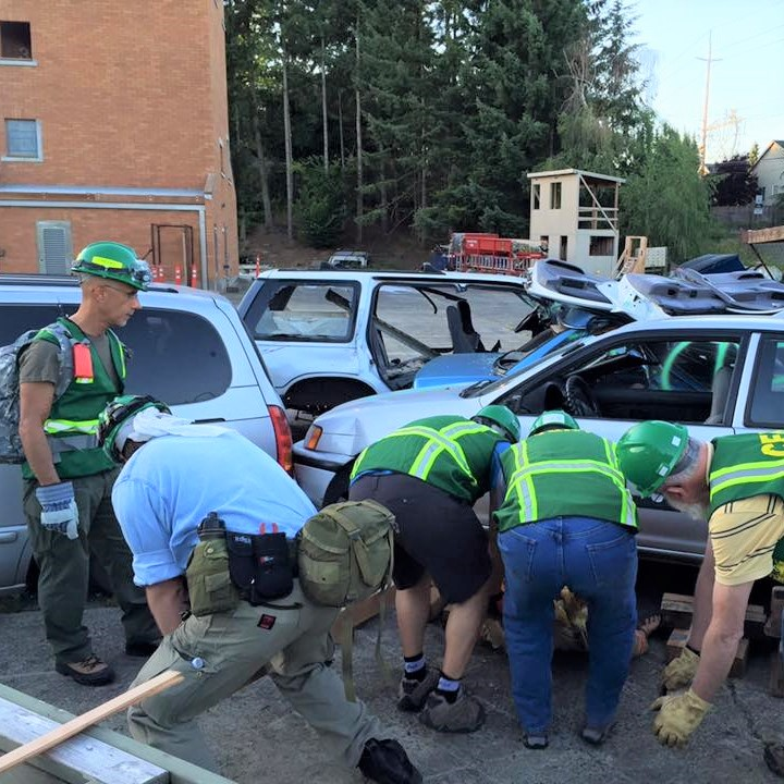 Clark County CERT volunteers get trained on cribbing. Four people are attempting to rescue a mannequin by lifting a car with wood blocks. A 5th person who is the trainer observes.