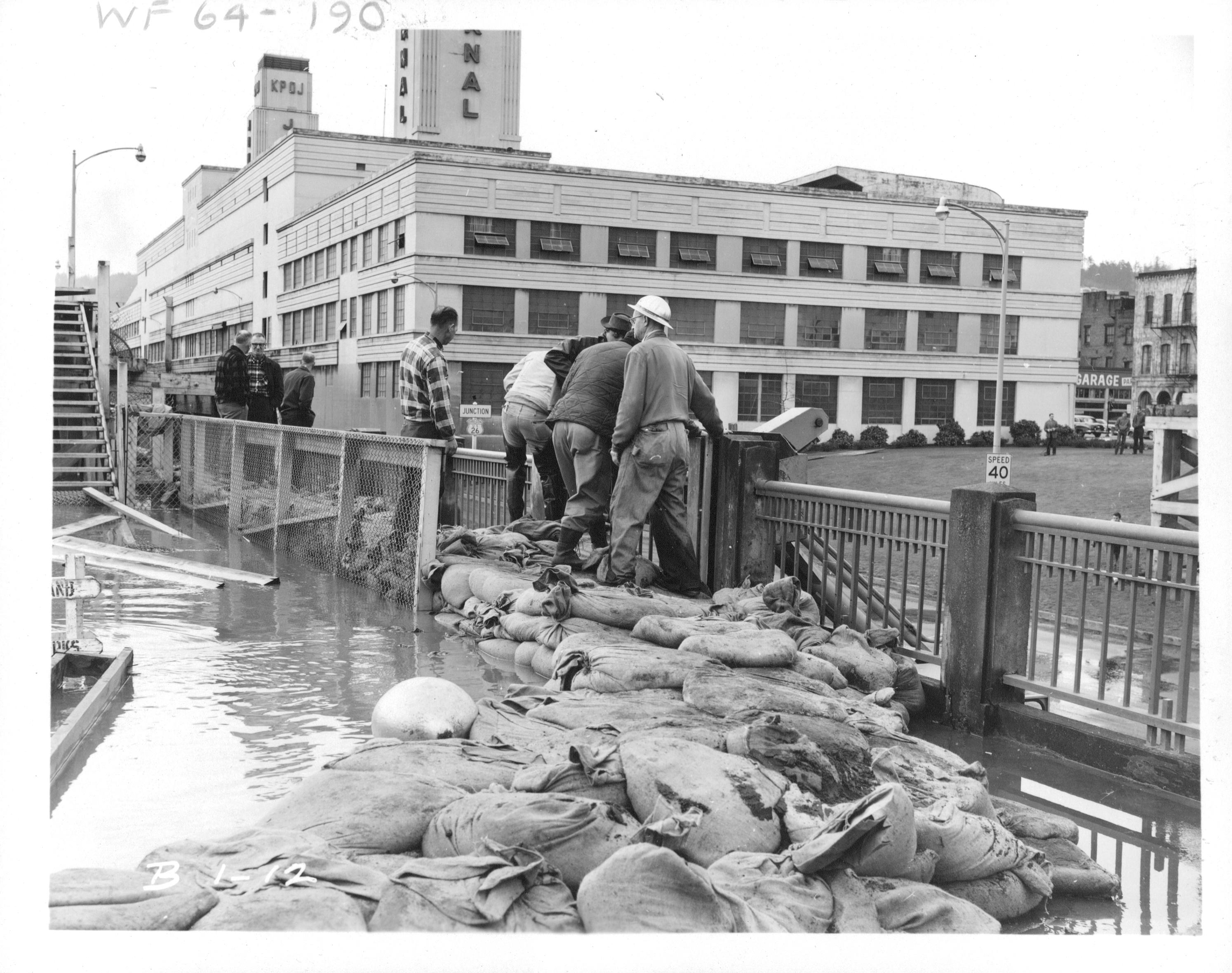 People are standing on a bridge looking down over the edge. There is flood water and sand bags on the bridge behind them. The image is in black and white, and it's from the Christmas Flood of 1996.