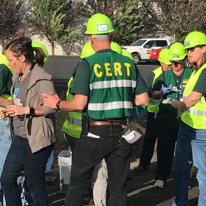 Community Emergency Response Team volunteers in green vests conduct a drill. A man in a vest escorts a volunteer who is pretending to be a disaster survivor.