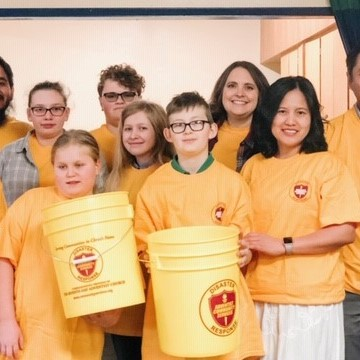 Children in Columbia County create disaster buckets at a preparedness event. A group of them are standing together smiling and wearing matching yellow shirts. Two of them hold buckets.