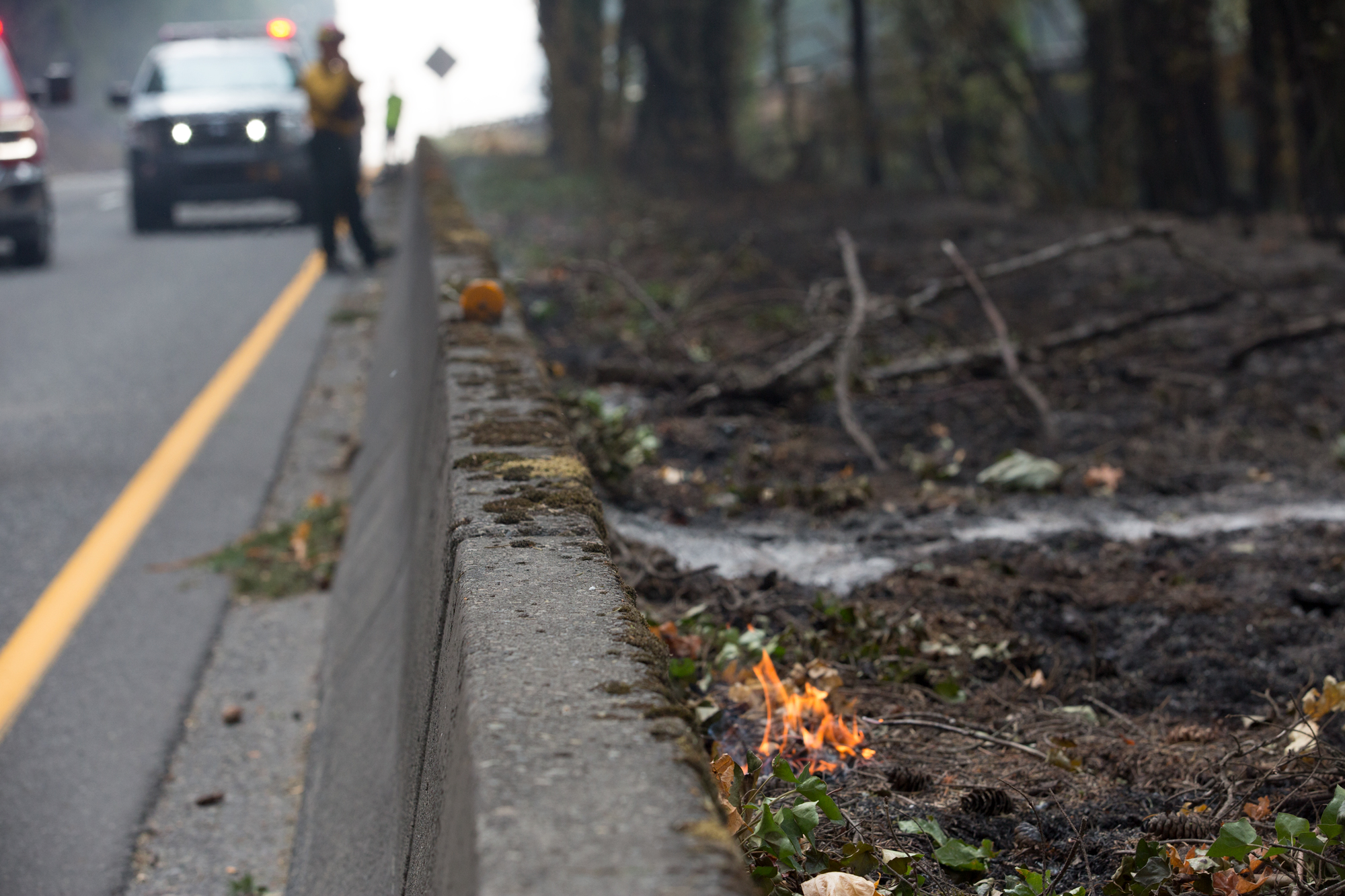 Photo of roadside during Eagle Creek Fire of 2017. Image shows smoke and forest ranger directing traffic.
