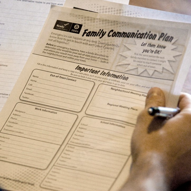 "Hands hold papers and pen. The paper says ""Family Communication Plan."""