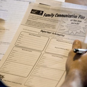 Person holds copy of FEMA family communication plan document.