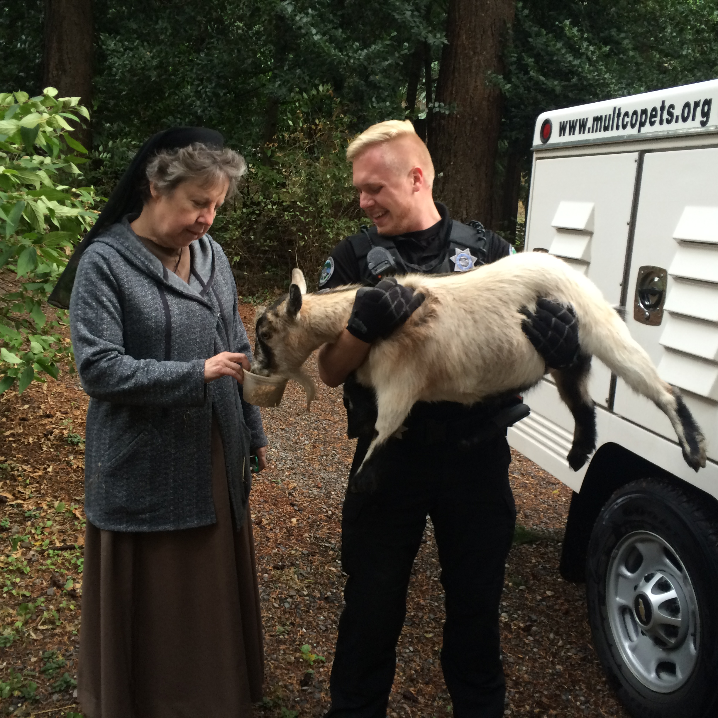 Photo of animal control officer holding a goat as a nun feeds the goat. The photo is from the 2017 Eagle Creek Fire.