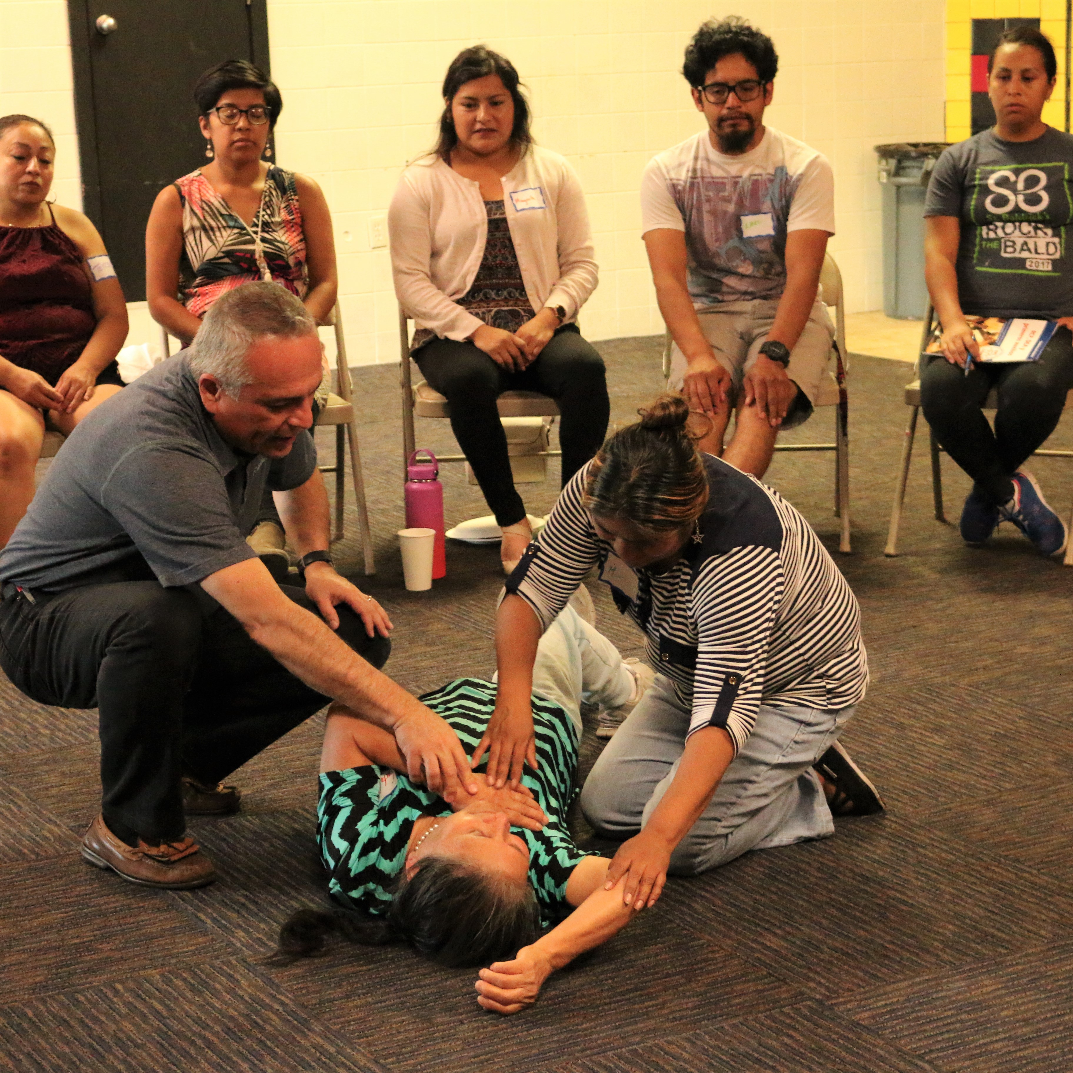 LISTOS volunteers receive CPR training in Portland's Cully neighborhood. An instructor shows a participant how to check the airway of victim volunteer. Several participants sit behind them and watch.