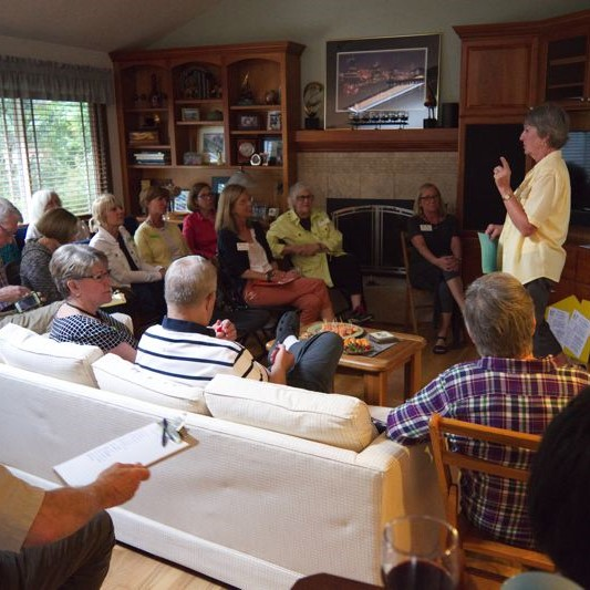 Neighbors meet to discuss emergency preparedness. They are in a living room, and a woman is standing up talking to others who are seated.