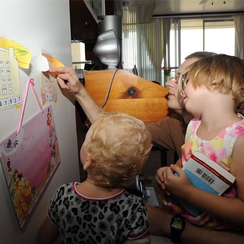 Man shows two small children how to dial their phone number using a drawing of a telephone on the wall. The man and young girls are white.