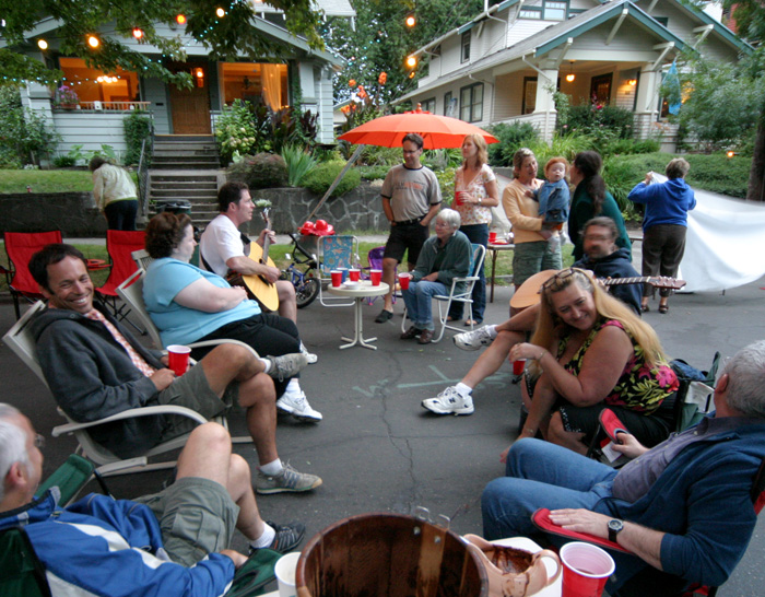 Neighbors sit in lawn chairs and stand around during a block party.