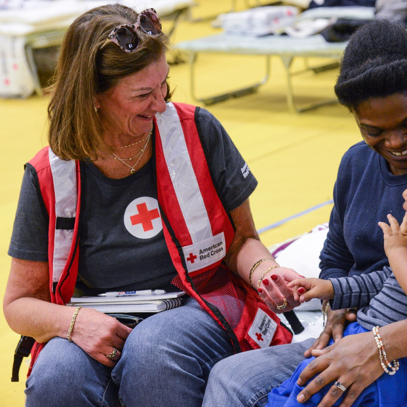 A Red Cross volunteer in a red and white vest sits on a cot with a woman and baby. They are talking and smiling.