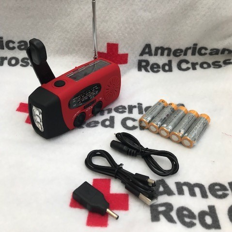 Red emergency radio sits on a Red Cross branded blanket. Next to the phone are charging cables, and adapter, and extra batteries.