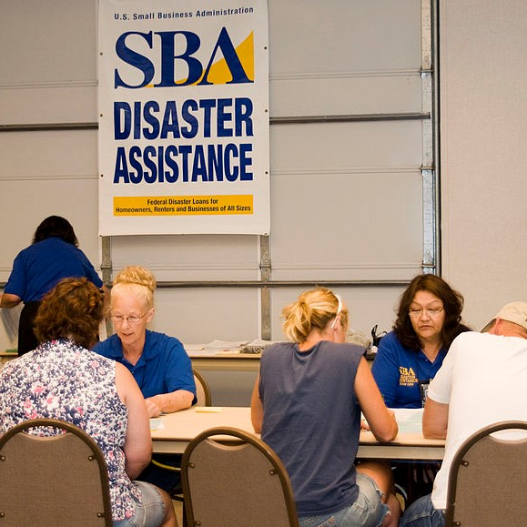 "Two women in blue shirts sit across the table from people who are applying for post-disaster assistance. The sign behind them says ""Small Business Association Disaster Assistance."""