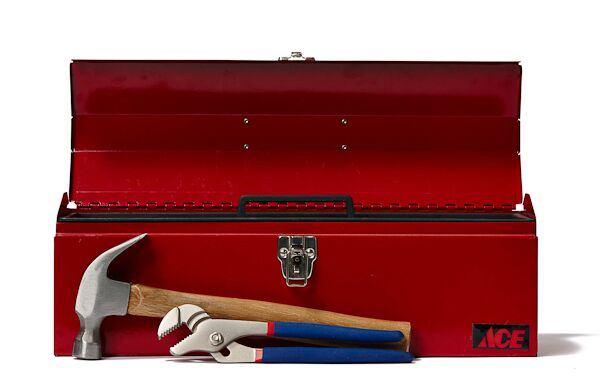 Red toolbox with a hammer and wrench in front of it