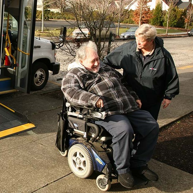 Man in a wheelchair is being assisted off a bus by a female TriMet employee.