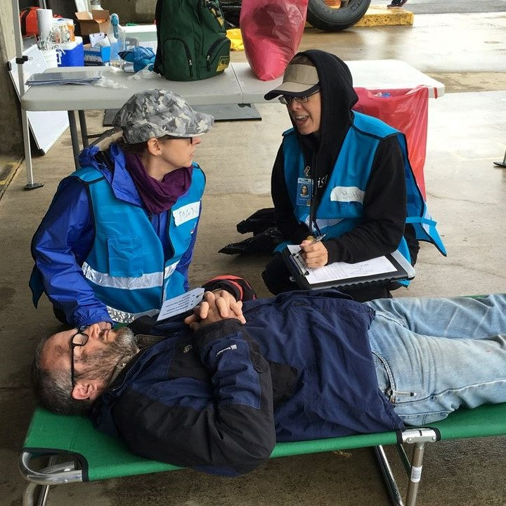 Medical Reserve Corps volunteers in blue vests conduct a drill. Two MRC volunteers are kneeling beside a cot and talking. A man is laying on the cot pretending to be injured.
