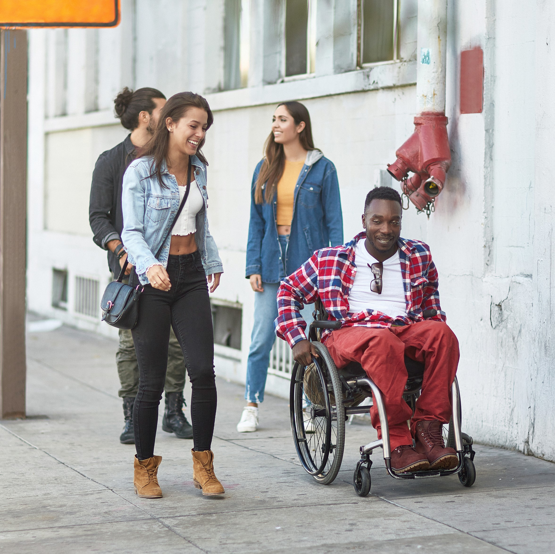 Man in a wheelchair traveling on a sidewalk next to friends who are walking. All are smiling.