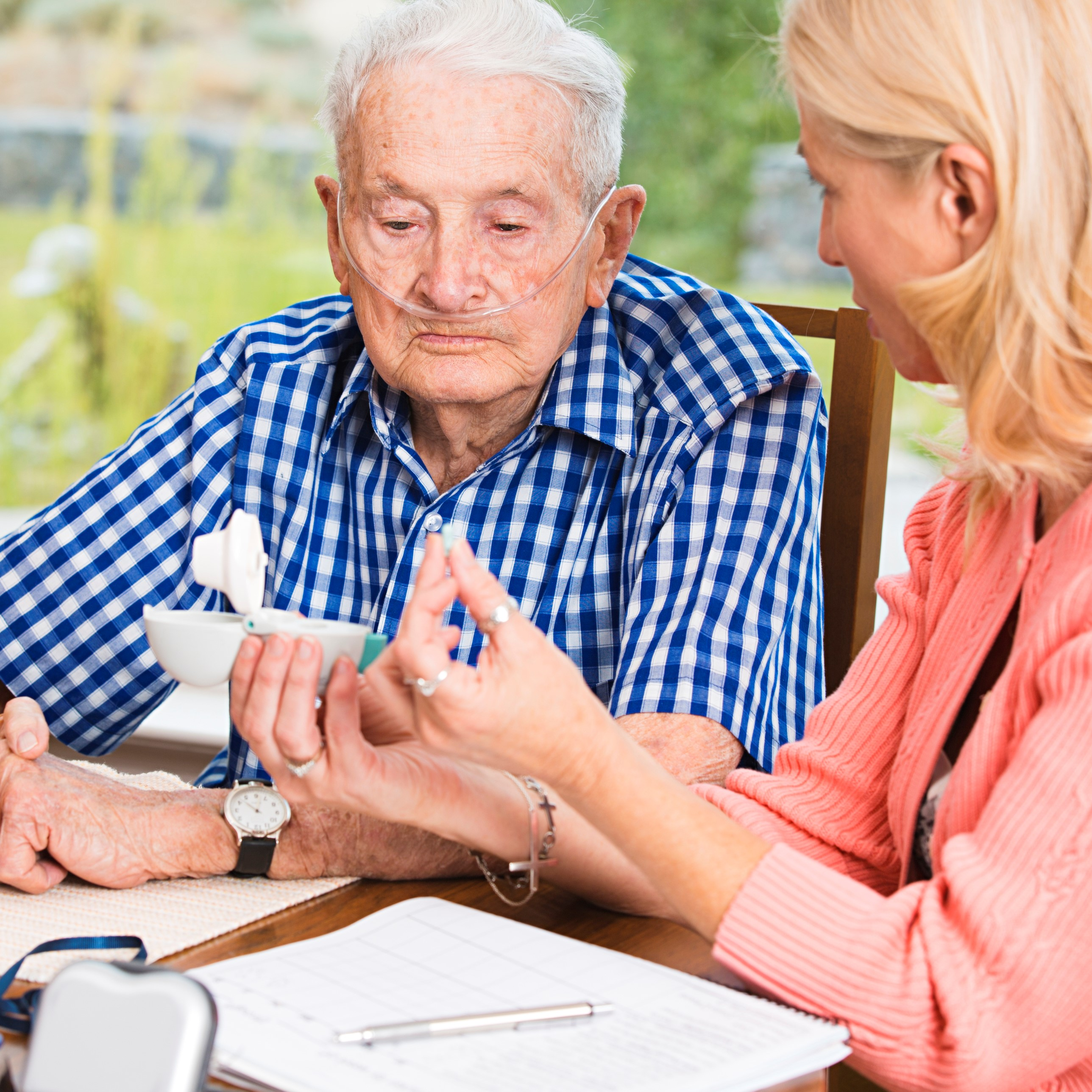 Elderly man sits at a table with a woman. She is showing him the details of his medication.