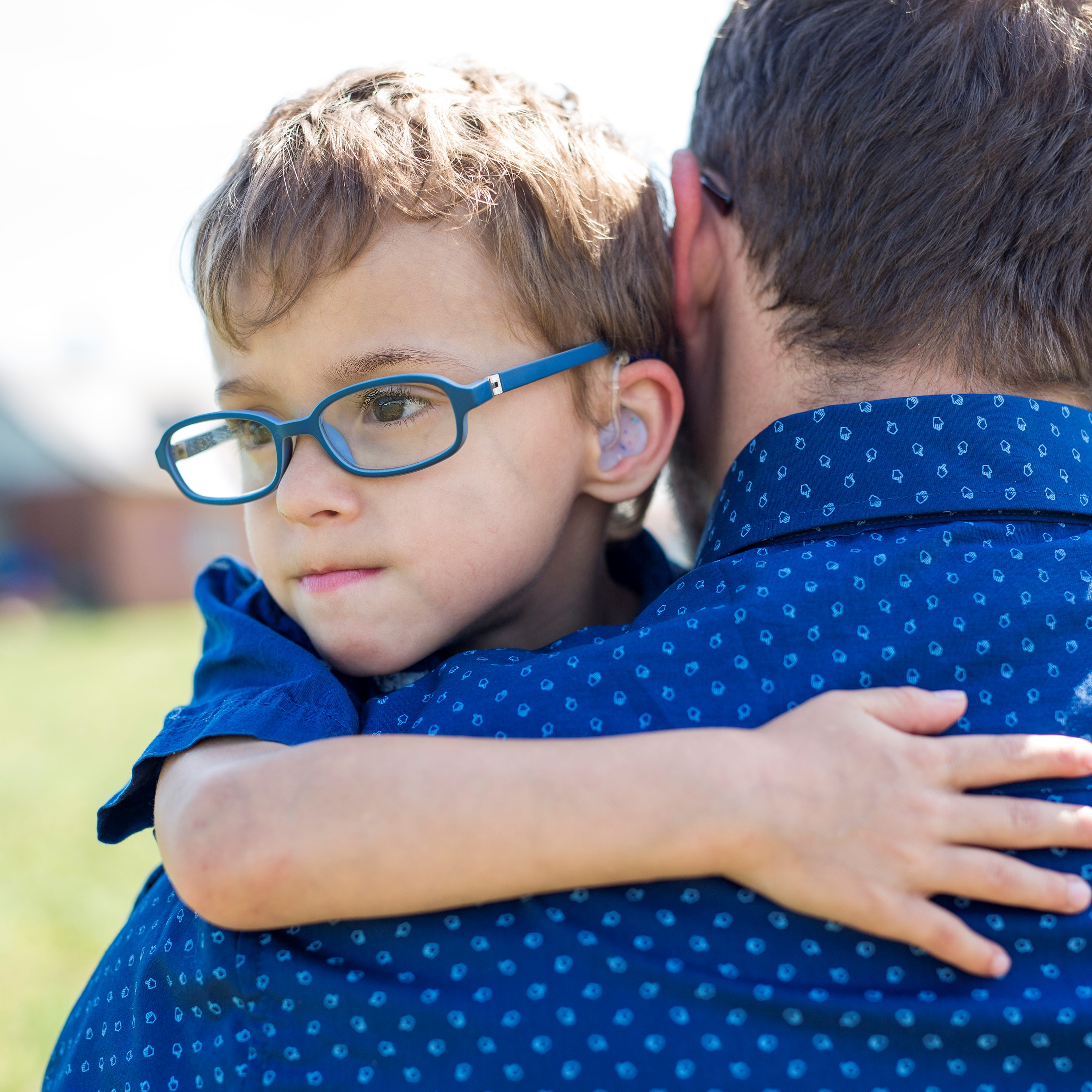 Young boy approximately four years hold is being held by a man. We see the boy's face but not the man's face. The boy has blue glasses and brown hair and seems a little sad.