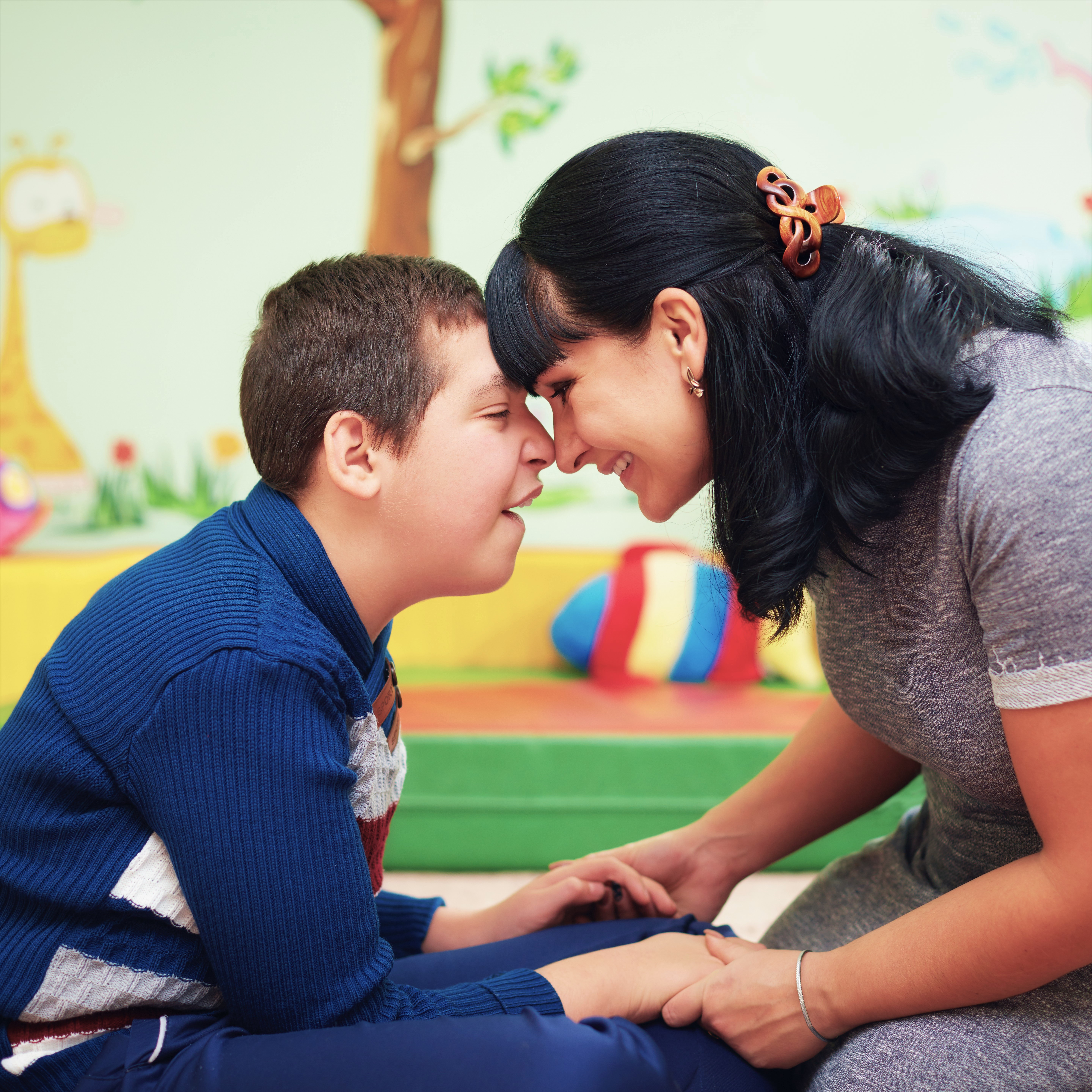 Child with cognitive disability touches his forehead to a woman's forehead. They are both smiling and seem very happy.