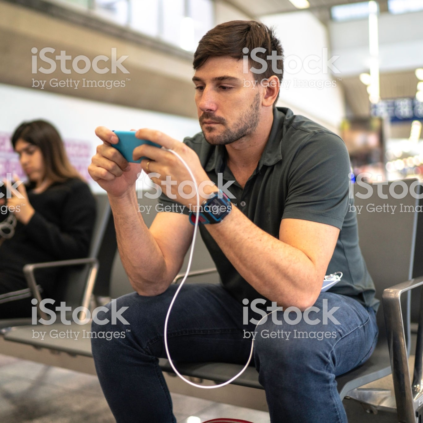 Man using and charging phone. He is holding a blue cell phone and appears to be typing. The phone is plugged into a portable battery, which is on his lap. He is a white man with brown hair and a short beard.