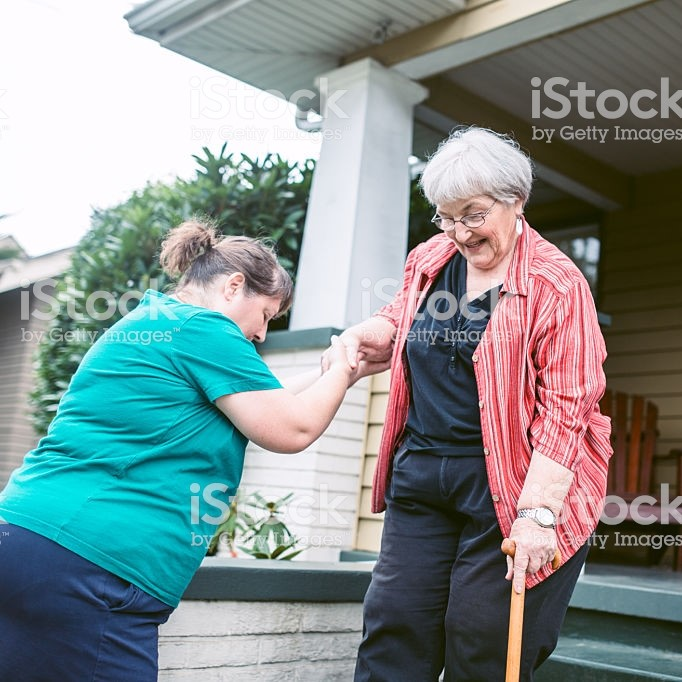 One neighbor helps another neighbor down steps in front of a house. Both are older white women.