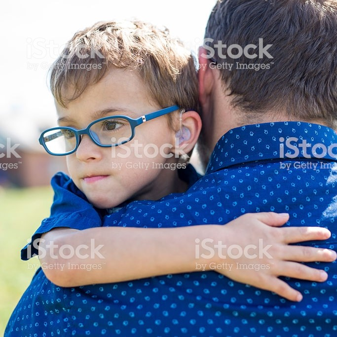 Young boy approximately four years hold is being held by a man. We see the boy's face but not the man's face. The boy has blue glasses and brown hair and seems a little sad. Both man and boy are white.