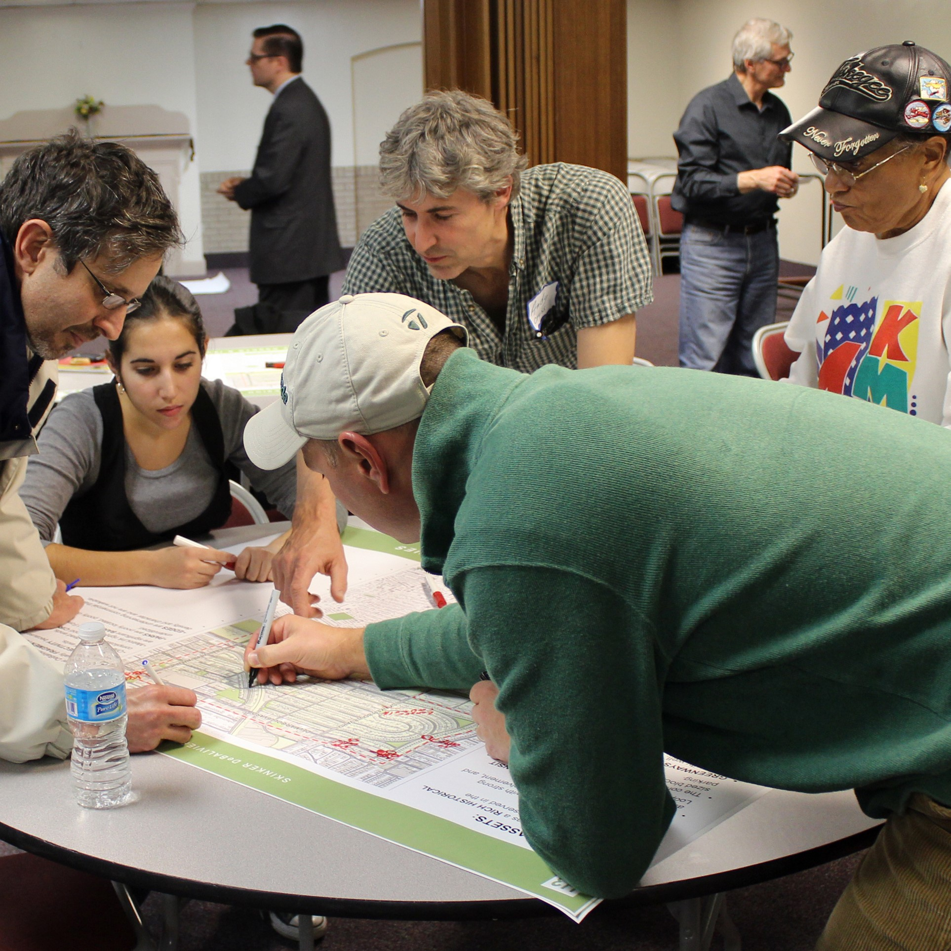 Community members make plans for their neighborhood. Med and women are standing around a table looking at a map.